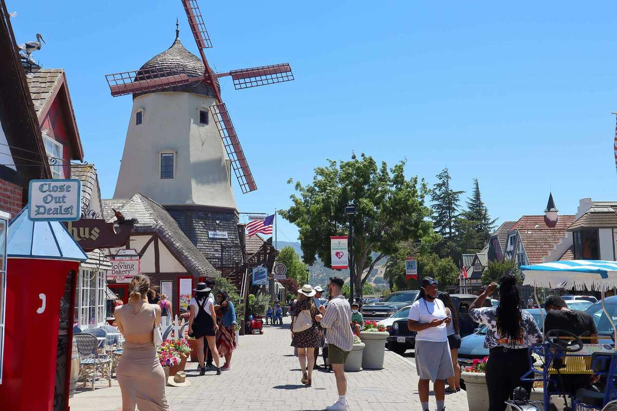 Tourists take photos of a windmill in Solvang, CA on June 26, 2021