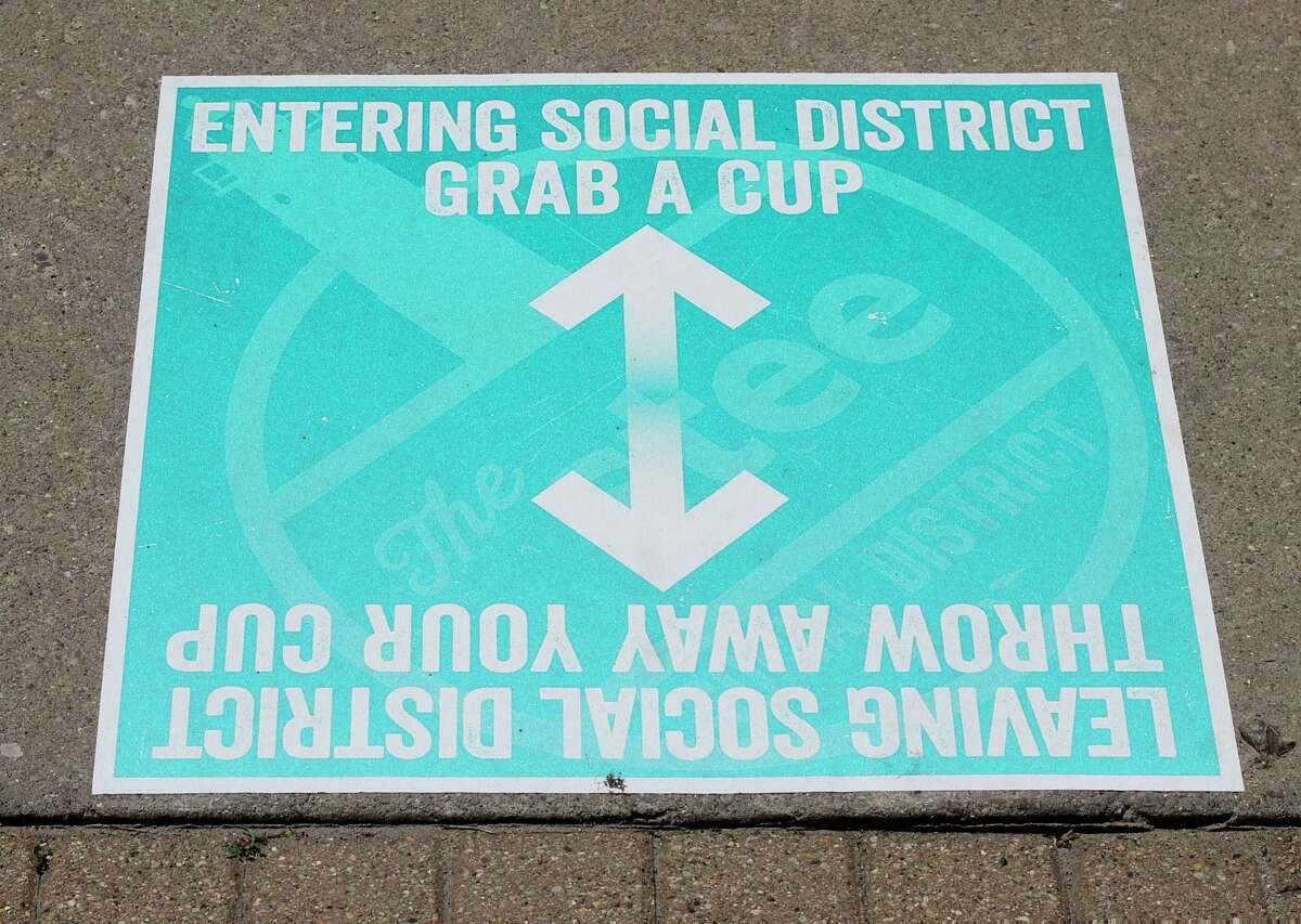 Teal sidewalk signs marklocation of Manistee's downtown social district. (Kyle Kotecki/News Advocate)