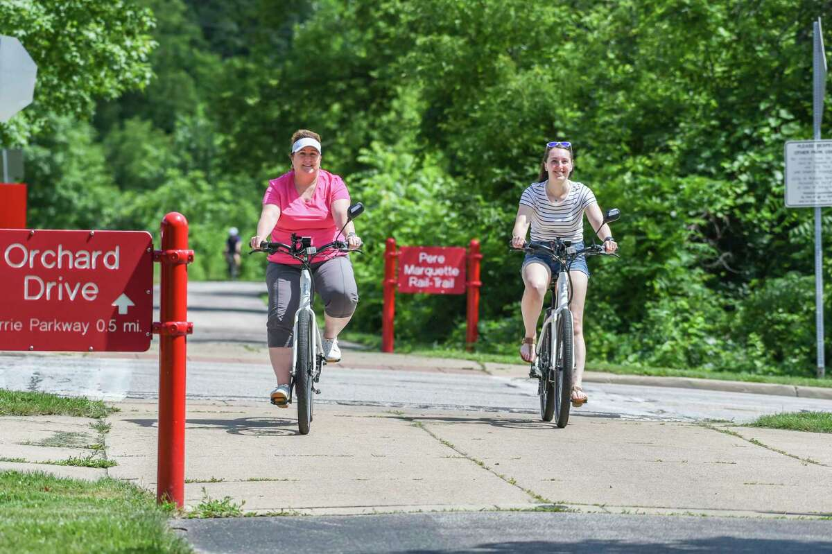 Julie and Katie Kramer bike along the trail Thursday afternoon. (Adam Ferman/For the Daily News)