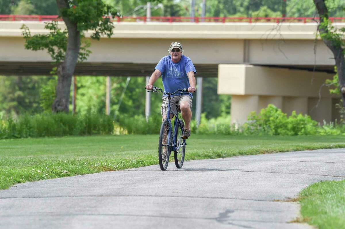 Rex Ainslie is pictured biking along the trail Thursday in Midland. (Adam Ferman/For the Daily News)