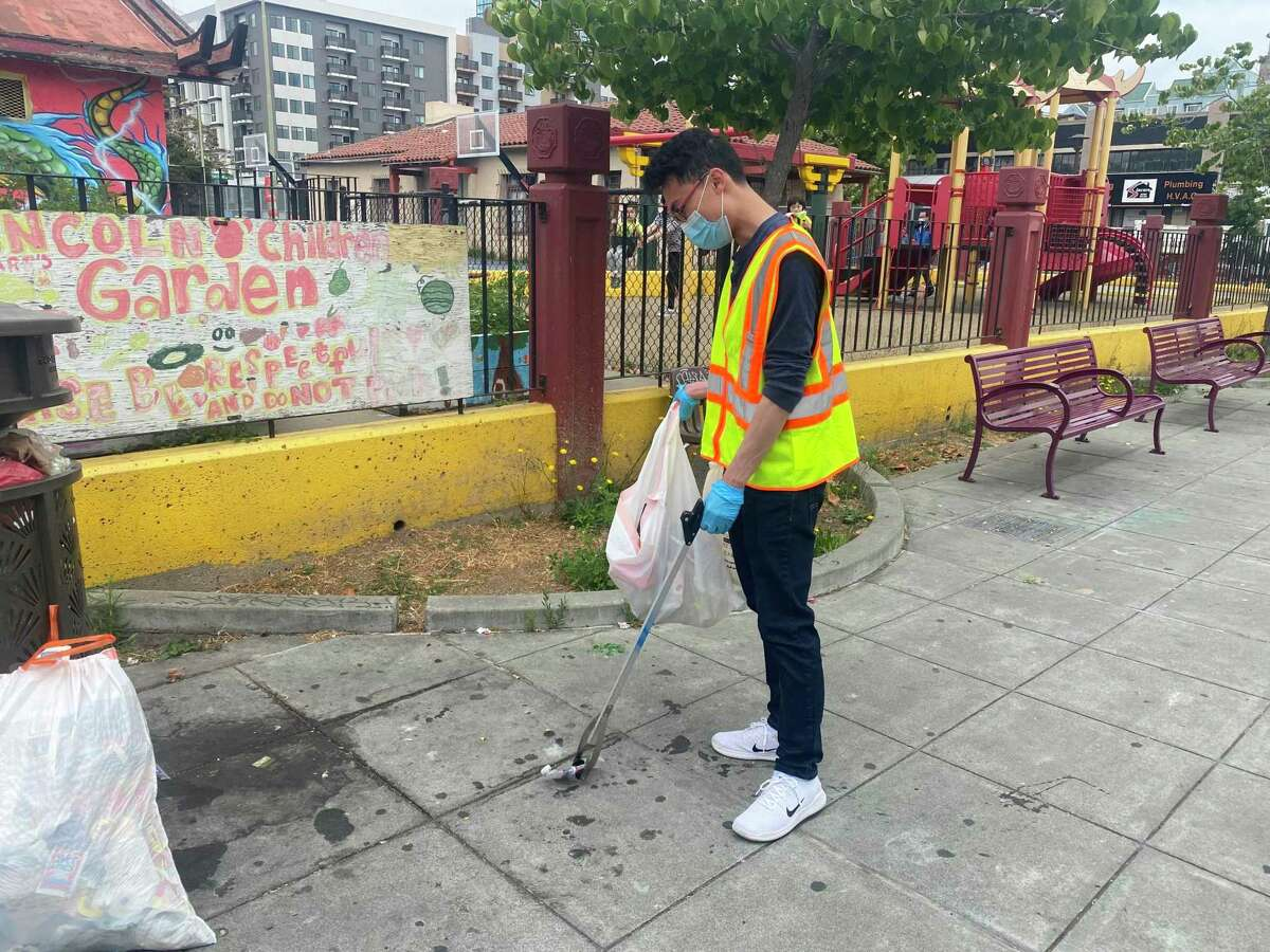 Volunteer Matthew Lee collects trash at Lincoln Square Park in Oakland.