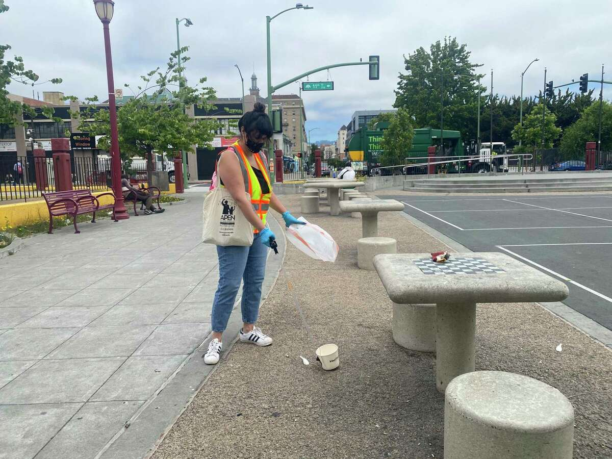 Volunteer Amanda Farrell collects trash at Lincoln Square Park in Oakland.