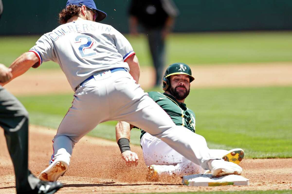 Oakland Athletics' Mitch Moreland is forced out at 3rd base by Texas Rangers' Charlie Culberson to end 2nd inning during MLB game at Oakland Coliseum in Oakland,, Calif., on Thursday, July 1, 2021.