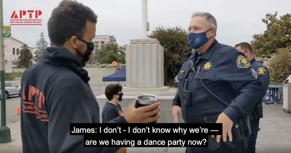 A screen capture from a video recording an encounter between Anti Police-Terror Project Police Director James Burch, left and Alameda County Sheriff's Sgt. David Shelby, right. Shelby is under investigation after he played a Taylor Swift song on his phone during the encounter, in an apparent attempt to ensure the recording of the incident would be automatically removed from social media sites like YouTube and Twitter.