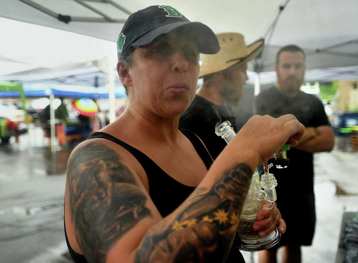 Tammy Crisp, of Manchester, lights up during the barbecue.