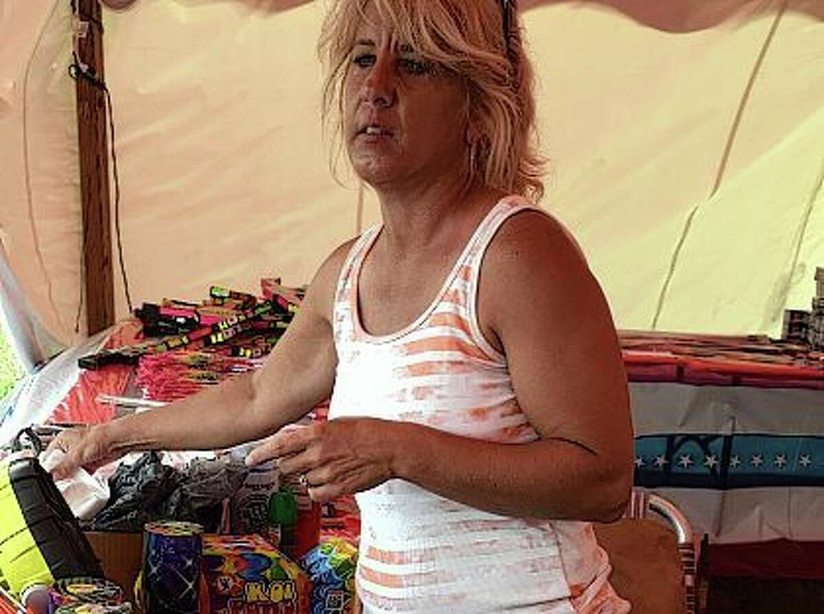Melissa Evans rings up a fireworks sale Thursday at the tent in front of Harbor Freight at 1813 W. Morton Ave.