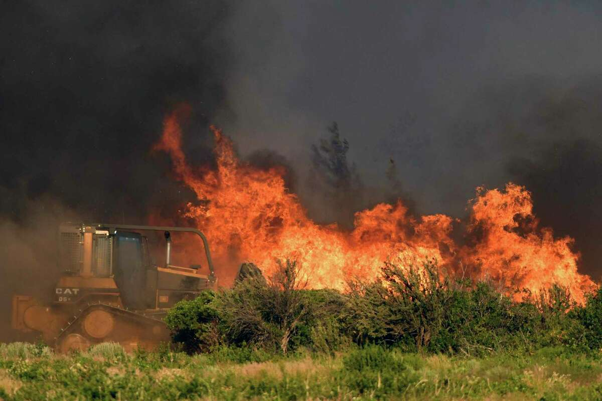 A bulldozer operator works on a fire line as vegetation burns nearby at the new Lava Fire.