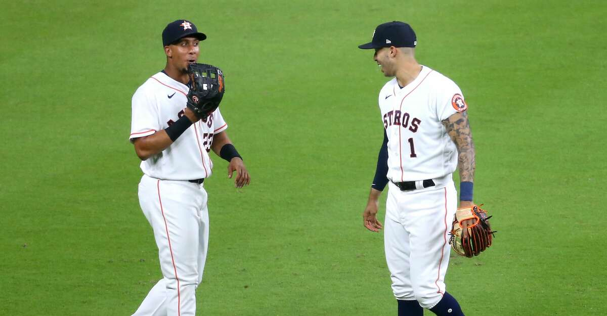 Houston Astros left fielder Michael Brantley (23) has some words with shortstop Carlos Correa (1) after he snagged a hit by Oakland Athletics catcher Sean Murphy (12) in the fourth inning at Minute Maid Park in Houston on Thursday, April 8, 2021.