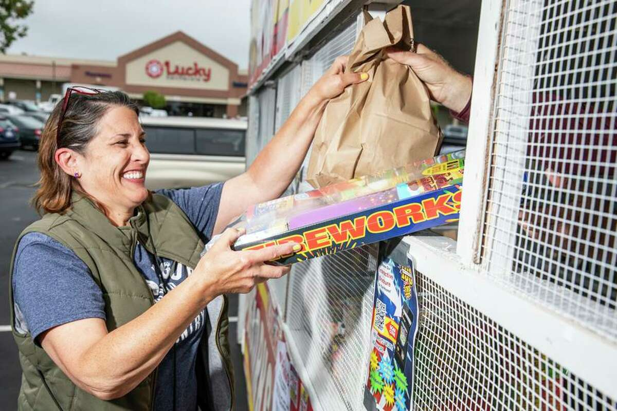 Above, Jennifer Lowery got fireworks at the TNT Fireworks booth in San Bruno, aiming to set them off in the street.