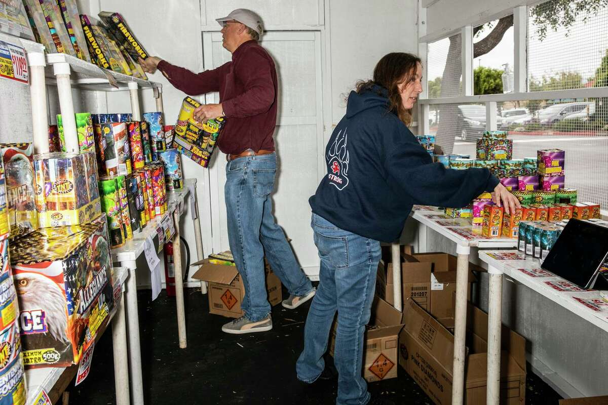 Bob Luttrell, committee chair of Scout Troop 72 and 4172 of San Bruno, and volunteer Kathie Laupati work inside a TNT Fireworks booth in the parking lot of San Bruno Towne Center.