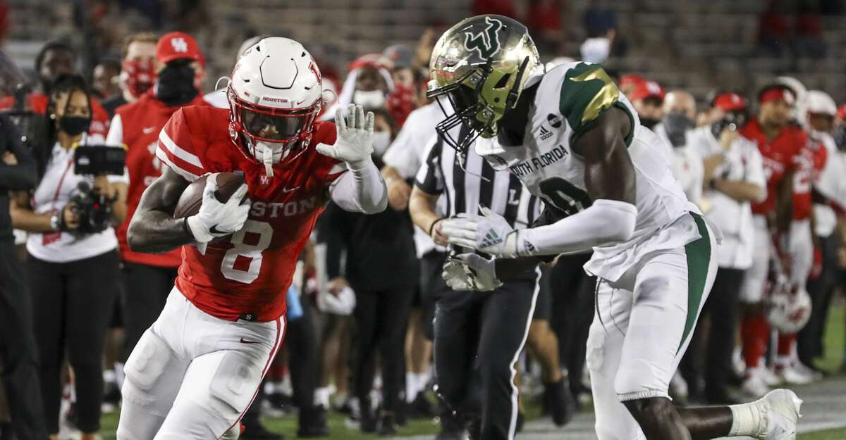 Houston Cougars running back Chandler Smith (8) gets pushed out of bounds by South Florida Bulls defensive back Daquan Evans (0) during the fourth quarter of an NCAA football game Saturday, Nov. 14, 2020, at TDECU Stadium in Houston.