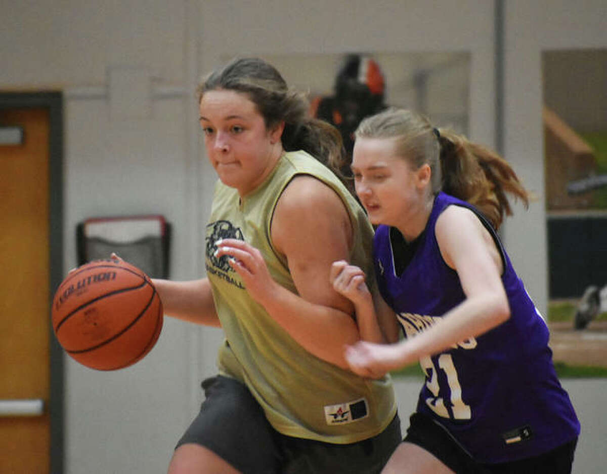 Father McGivney senior Charlize Luehmann shields the ball away from a Collinsville defender as she brings the ball up the court Tuesday in Edwardsville.
