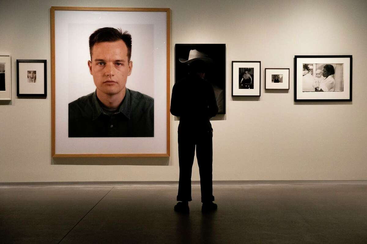 """Austin Leong sees the """"About Face"""" gallery at Pier 24 Photography on Thursday in San Francisco. The reopening exhibition is """"Looking Back,"""" a retrospective on the private museum's first decade."""