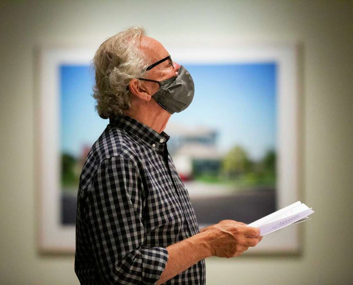 """Eric Watterud checks out the """"Close to Home"""" gallery at Pier 24 Photography on Thursday in San Francisco. The re-opening exhibition is """"Looking Back,"""" a retrospective on the private museum's first decade."""