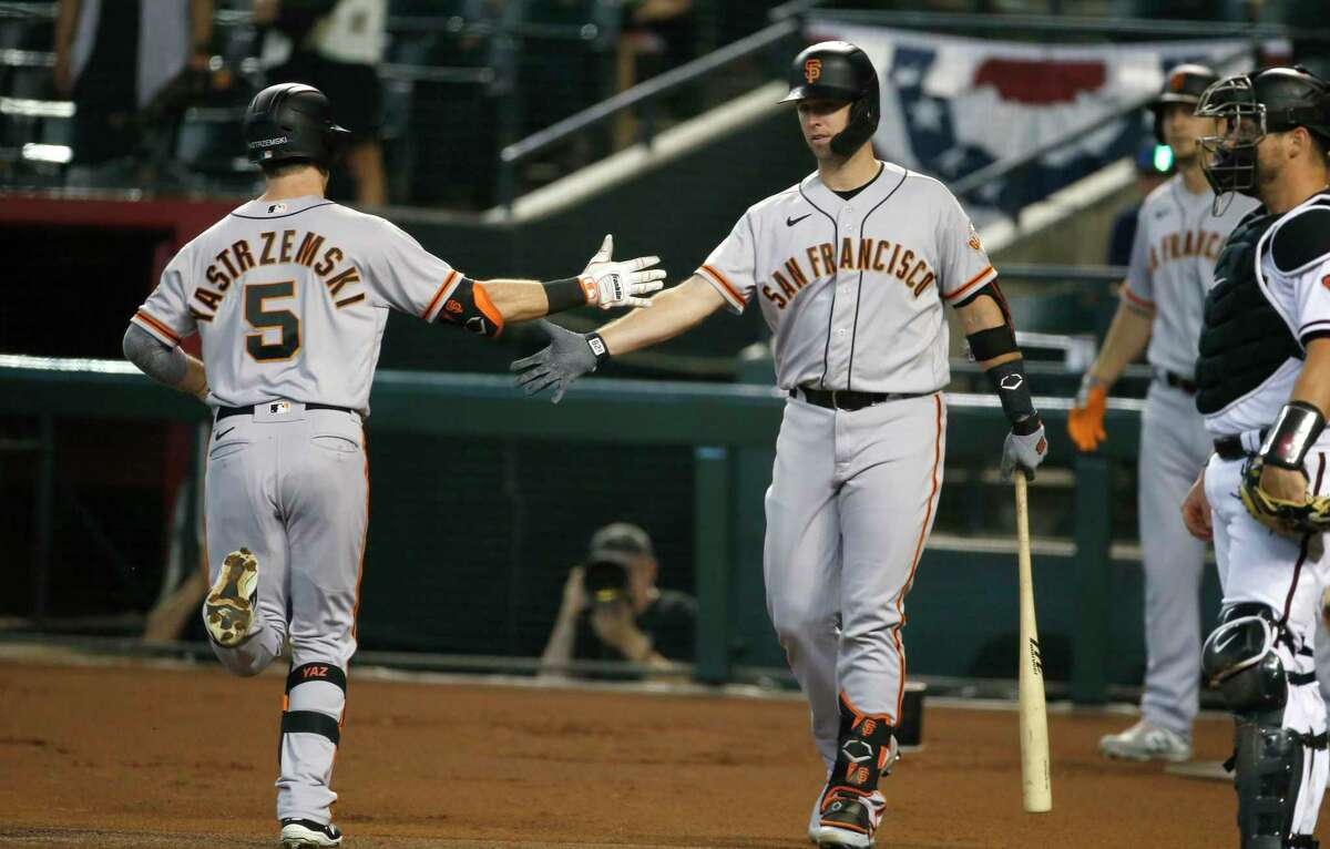 PHOENIX, ARIZONA - JULY 01: Buster Posey #28 of the San Francisco Giants congratulates Mike Yastrzemski #5 of the Giants after his solo home run against the Arizona Diamondbacks during the first inning of the MLB game at Chase Field on July 01, 2021 in Phoenix, Arizona. (Photo by Ralph Freso/Getty Images)