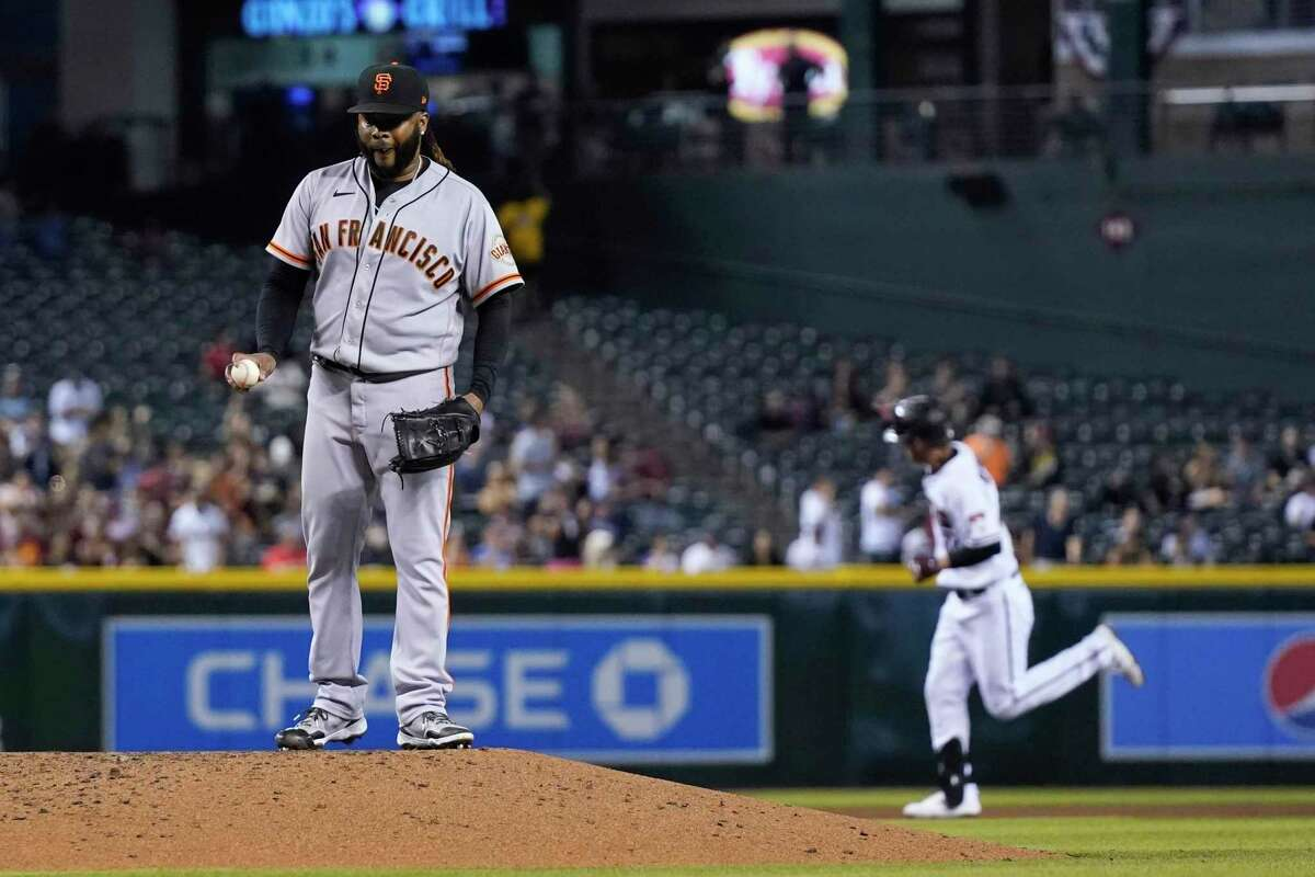 San Francisco Giants starting pitcher Johnny Cueto, left, holds a new baseball after giving up a two-run home run to Arizona Diamondbacks' Josh Reddick, right, during the fourth inning of a baseball game Thursday, July 1, 2021, in Phoenix. (AP Photo/Ross D. Franklin)