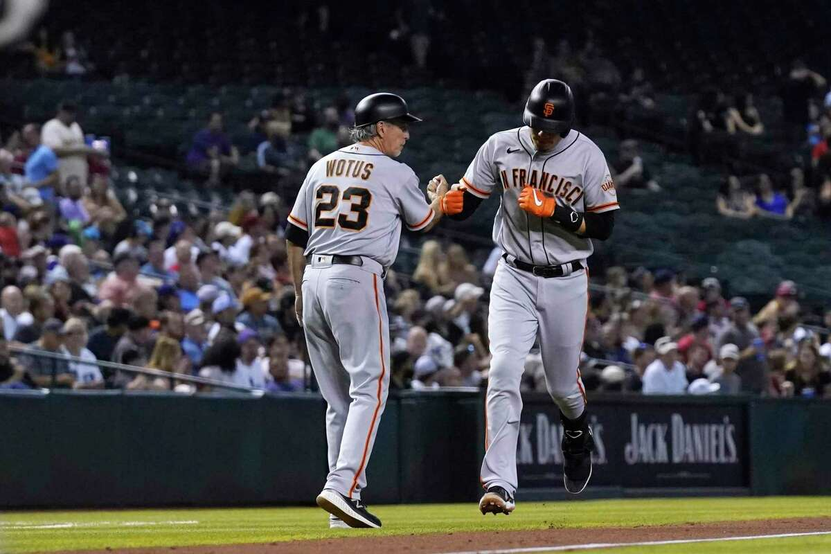 San Francisco Giants' Wilmer Flores, right, celebrates his two-run home run against the Arizona Diamondbacks with third base coach Ron Wotus (23) during the fourth inning of a baseball game Thursday, July 1, 2021, in Phoenix. (AP Photo/Ross D. Franklin)