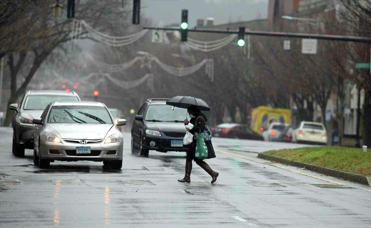 A pedestrian crosses Main Street, in Danbury, Conn, in the rain in this file photo.