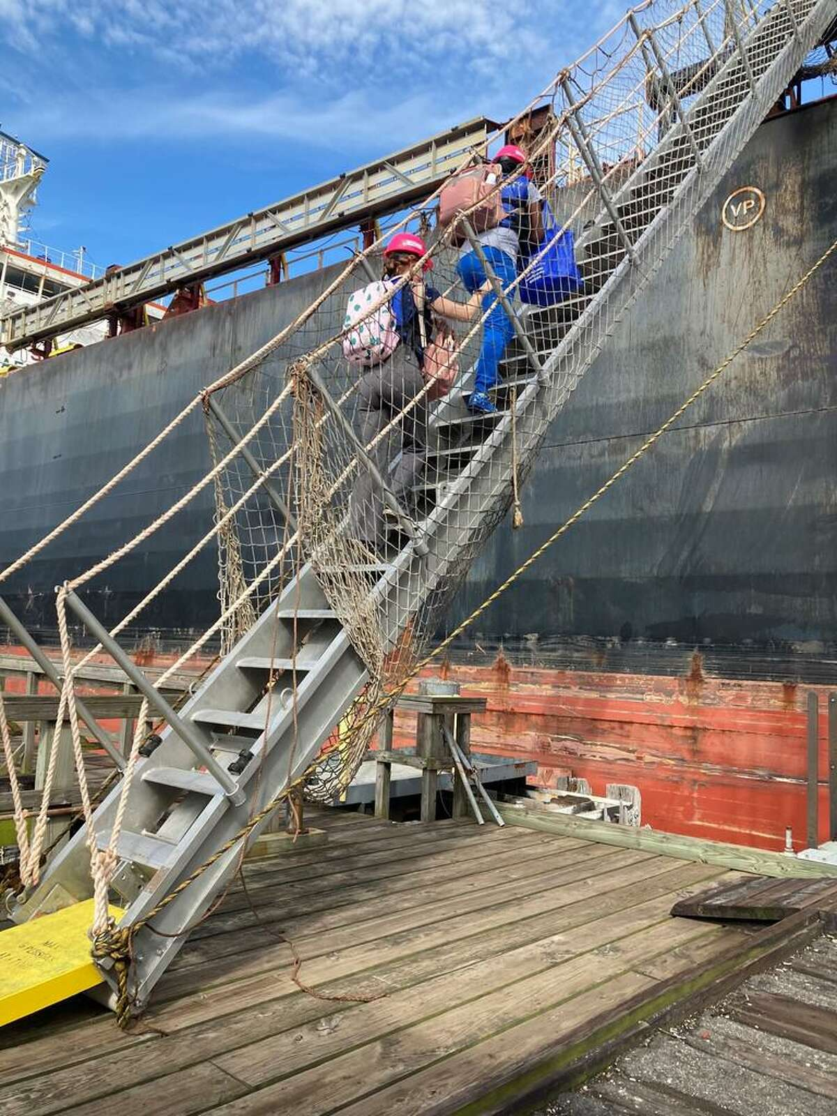 RN Tasheaka Jones, and Patient Registrar DeAnna Andrews, climb the ladder to the ship.