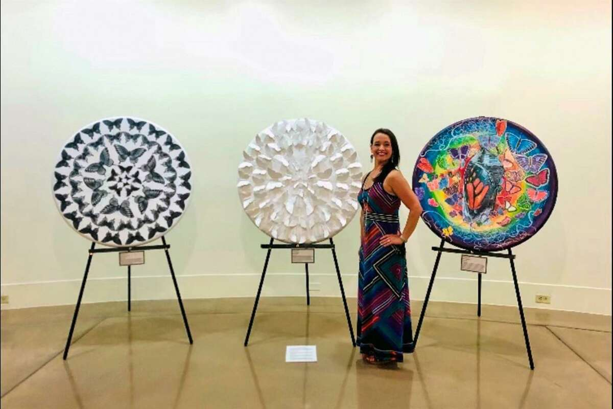 """Cypress Ridge High School art teacher Shawna Billet poses next to her works of art that she contributed to """"Pulse/49: A Texas Remembrance Exhibition."""" She joined four other artists for the exhibit, which honored the victims of the Pulse nightclub tragedy five years ago in Orlando, Fla. and was on display at the Texas State Capitol Building. Billet's three pieces, from left, were titled """"Into the Darkness,"""" """"Finding Light,"""" and """"Radiant Life."""""""
