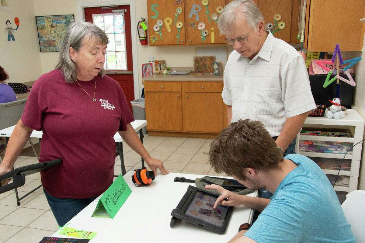 Debbie Rigsby encourages a New Danville Wrangler to show Walter Cooke his new ability to color a picture using specialized apps on an iPad purchased with a grant from the Madalyn Cooke Foundation.