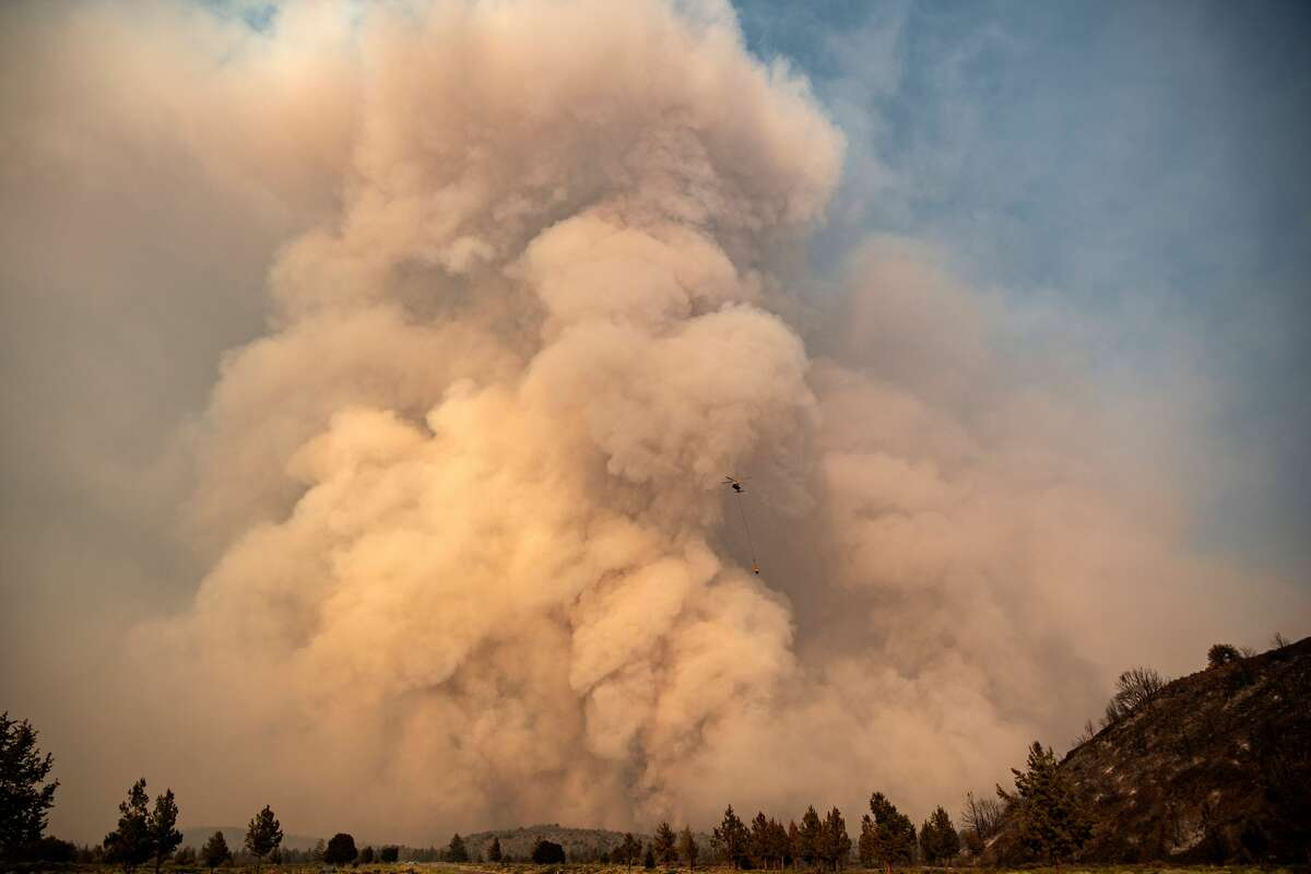 FILE - A water-dropping helicopter is dwarfed by a pyrocumulus ash plume as the Lava fire explodes in Weed, California on July 1, 2021. - Firefighters are battling nearly a dozen wildfires in the region following soaring temperatures in California's valley, mountain and desert areas, windy dry conditions, lightning storms across several parts of the western United States.