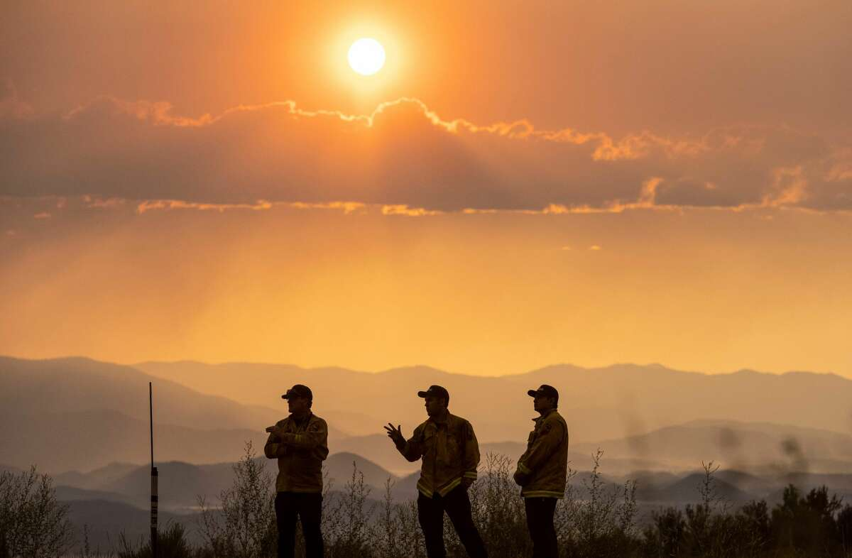 Firefighters monitor the scene as the Lava fire continues to burn in Weed, California on July 1, 2021. - Firefighters are battling nearly a dozen wildfires in the region following soaring temperatures in California's valley, mountain and desert areas, windy dry conditions, lightning storms across several parts of the western United States.