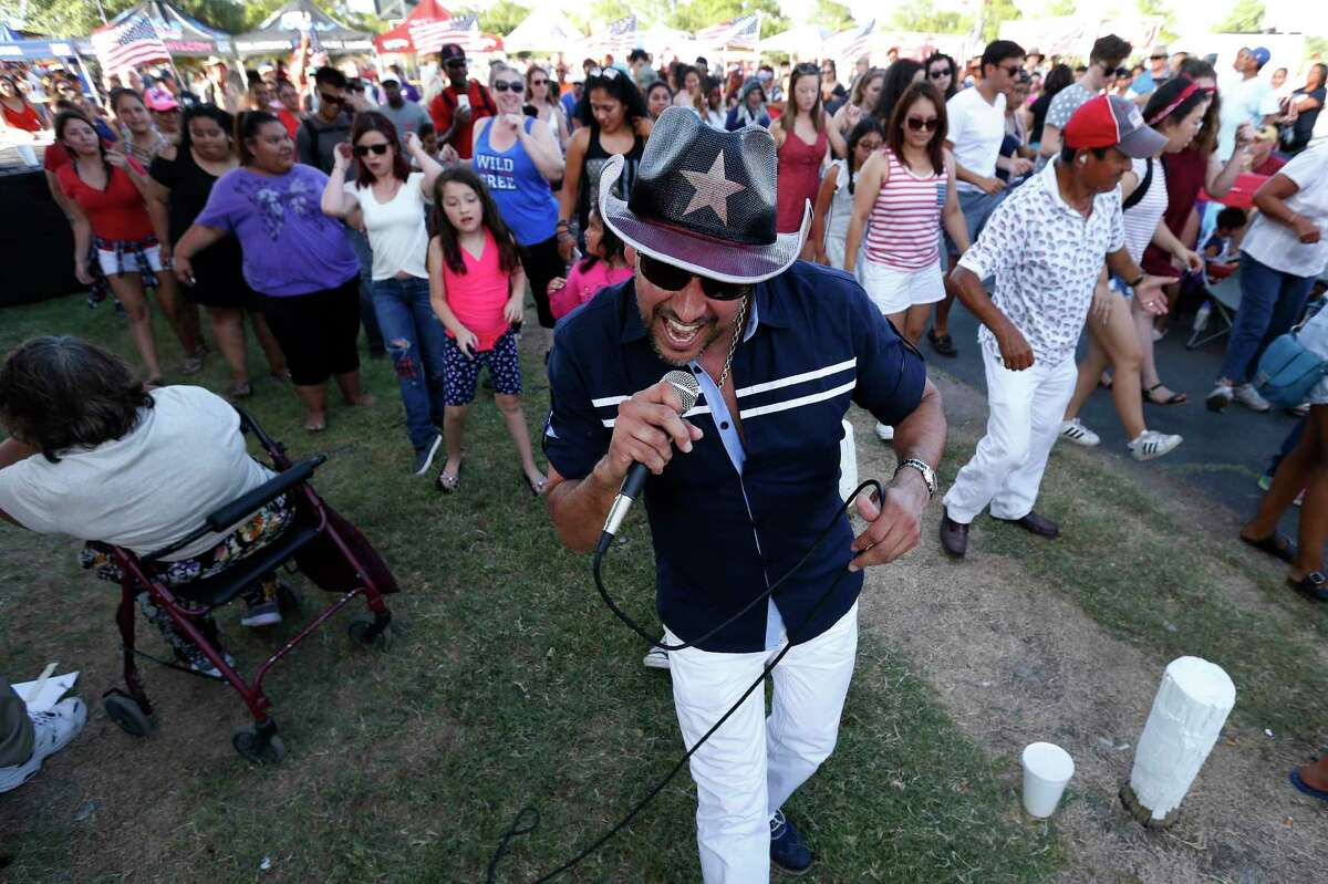 Esteban Cardenas leads a crowd in a line dance during Independence Day celebrations at Woodlawn Lake in 2017.