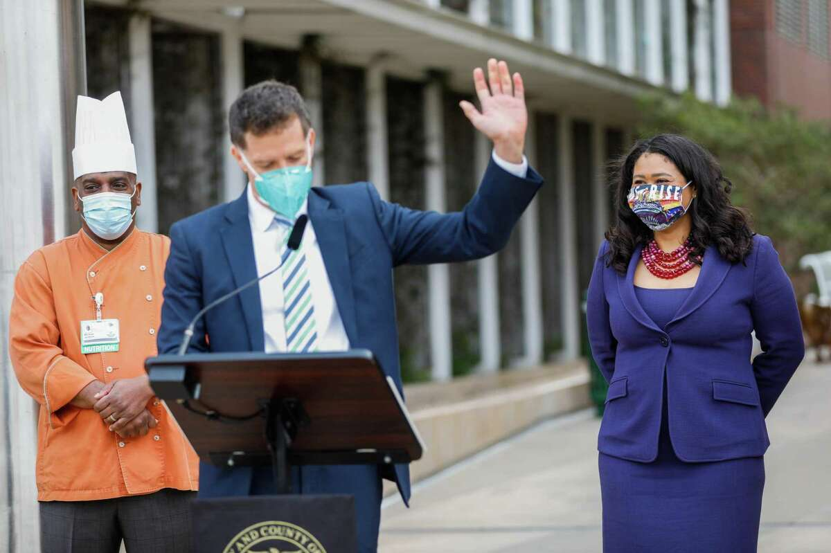 Mayor London Breed (right) listens as Dr. Grant Colfax, director of the San Francisco Department of Public Health, speaks at a news conference March 17.
