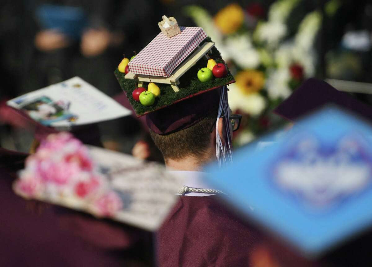 A miniature picnic adorns the cap of a graduate at the Bethel High School graduation ceremony in June 2021 in Bethel, Conn. On Friday, July 2, the U.S. Department of Labor reported elevated levels of hiring by schools nationally, as many institute extra summer programs to help cover any learning gaps during the COVID-19 pandemic and otherwise provide extra support for families in their towns.