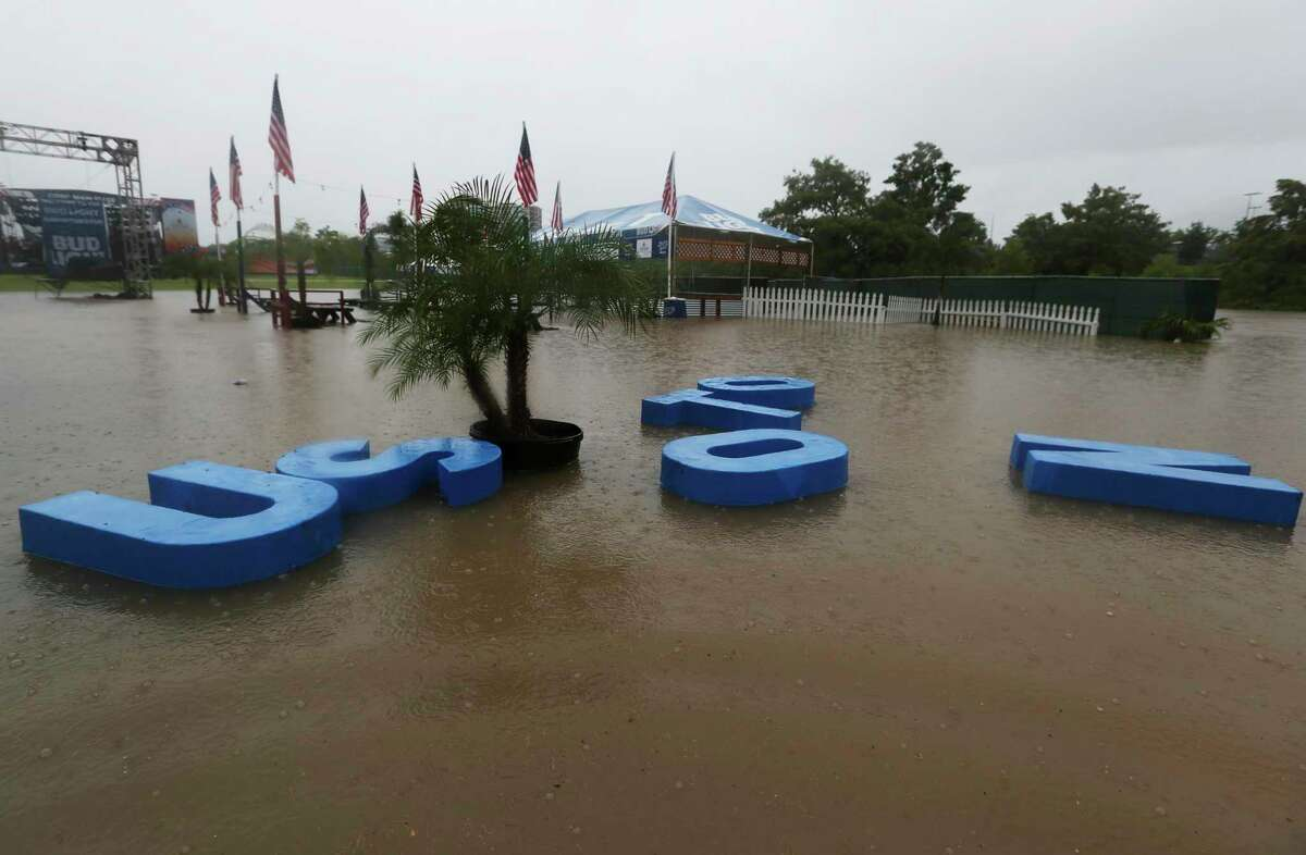 """The """"Houston"""" letter signs are floating away from the Budlight beach volleyball court as the water from Buffalo Bayou flooded Eleanor Tinsley Park on Wednesday, July 4, 2018, in Houston. Freedom Over Texas concert is cancelled due to the rain storm and flood of the location. ( Yi-Chin Lee / Houston Chronicle )"""