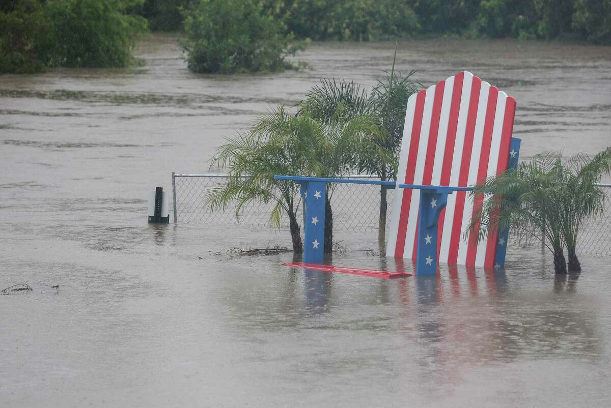 A giant lawn chair, painted in patriotic colors and stars, is under Buffalo Bayou floodwater after heavy rainfall on Wednesday, July 4, 2018, in Houston. The Freedom Over Texas concert was cancelled after Buffalo Bayou flooded and compromised Eleanor Tinsley Park. ( Yi-Chin Lee / Houston Chronicle )
