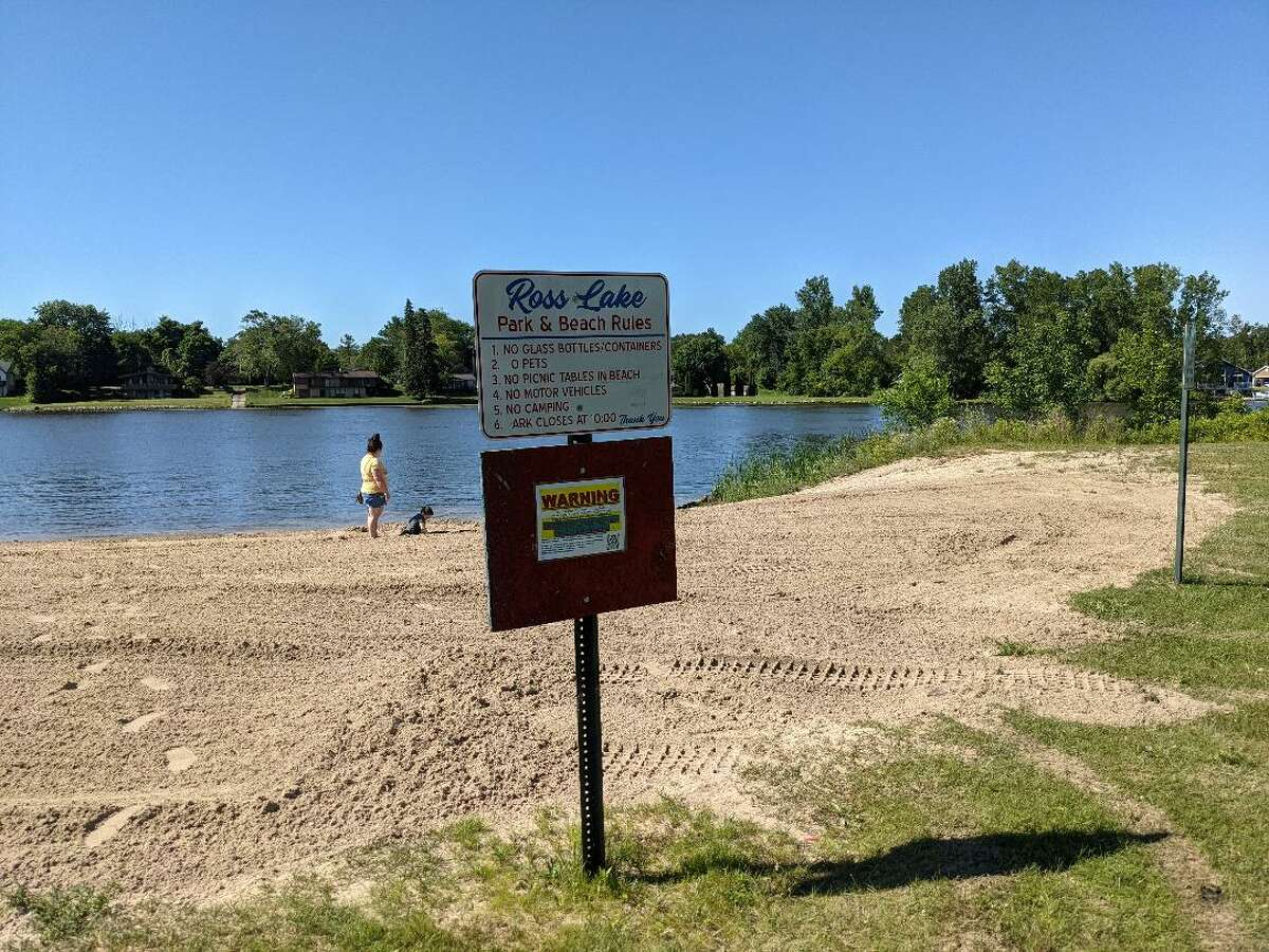 There were swimmers in Beaverton's Ross Lake Friday afternoon despite the warning noting high bacteria levels that were unsafe for swimming. One resident said the sign's low visibility wouldn't deter swimming. The beach is expected to stay closed through the holiday weekend, according to the Central Michigan District Health Department.