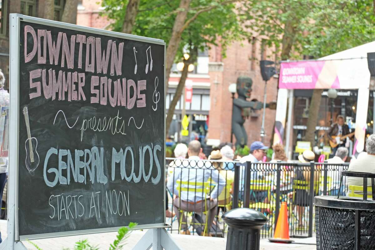 A sign welcomes park-goers to the day's performance of Downtown Summer Sounds featuring General Mojos in 2019.