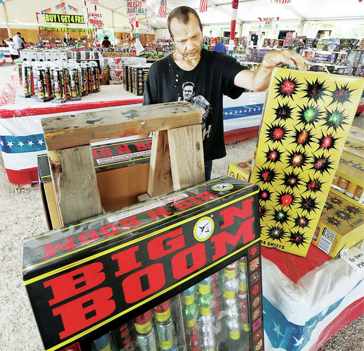 Jason Williams of Kampsville ponders the many fireworks choices Tuesday in the large fireworks tent in West Alton, Missouri where sales were steady.