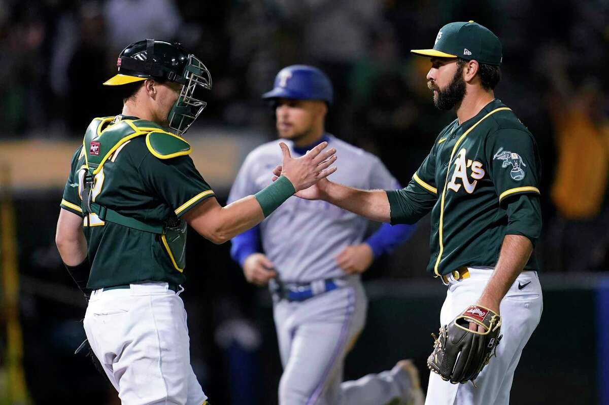 Oakland Athletics catcher Sean Murphy, left, celebrates with relief pitcher Lou Trivino after the Athletics defeated the Texas Rangers in a baseball game in Oakland, Calif., Wednesday, June 30, 2021. (AP Photo/Jeff Chiu)