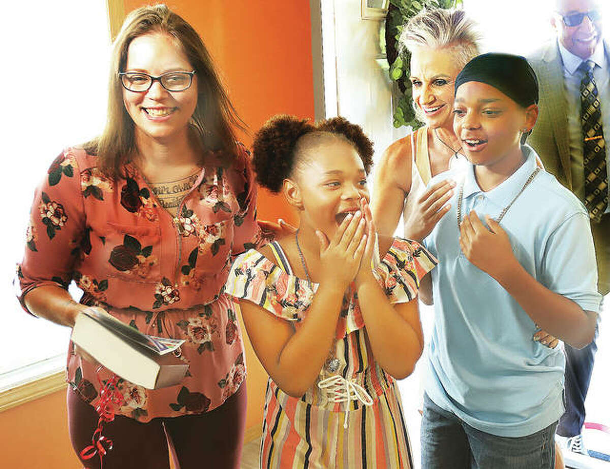 Natasha Krikelas, and her children, Tihana and Travon, get the first look inside their new home in Alton on Friday with Brenda Warner.