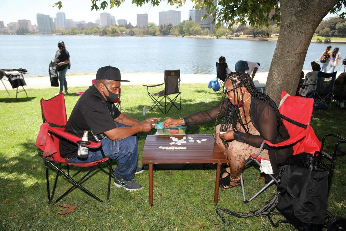 Michael Flemings, 67, of Stockton, plays dominoes with his daughter, Felita Flemings, 49, of San Francisco, at Lake Merritt in Oakland in 2020. Domino games are a familiar sight at many Black Bay Area family gatherings on the Fourth of July.