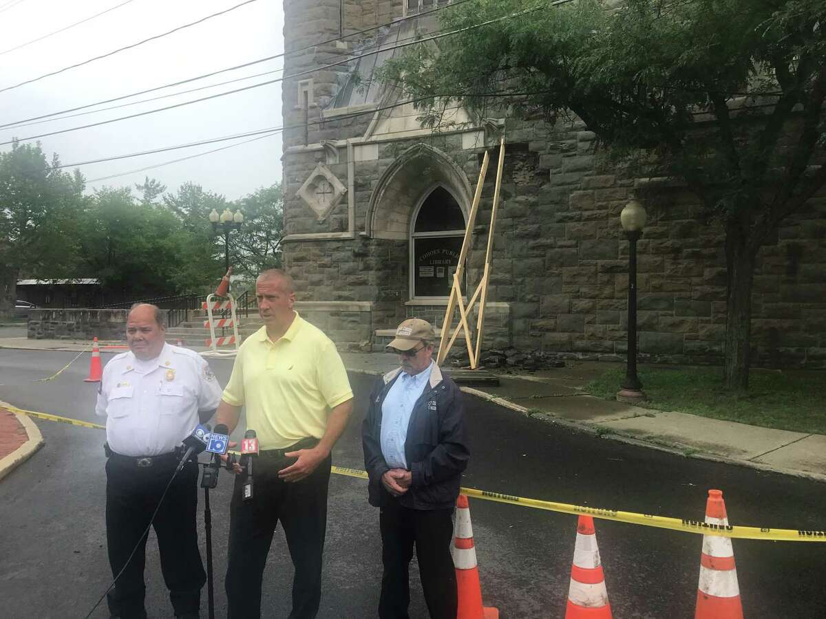 From left, Cohoes Fire Chief Joseph Fahd, Mayor Bill Keeler and City Engineer Gary Nathan stand in front of the damaged Cohoes Public Library in Cohoes, N.Y. on Friday July 2, 2021.