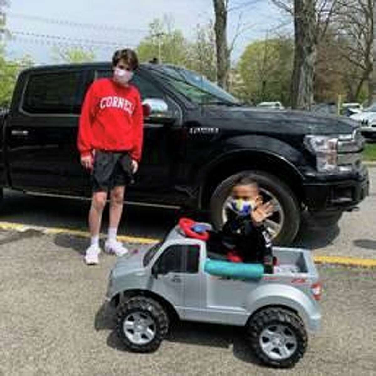 Leo Rosen, a resident of Purchase, N.Y., presents an F-150 retrofitted tiny truck to a 4-year-old student with special needs.