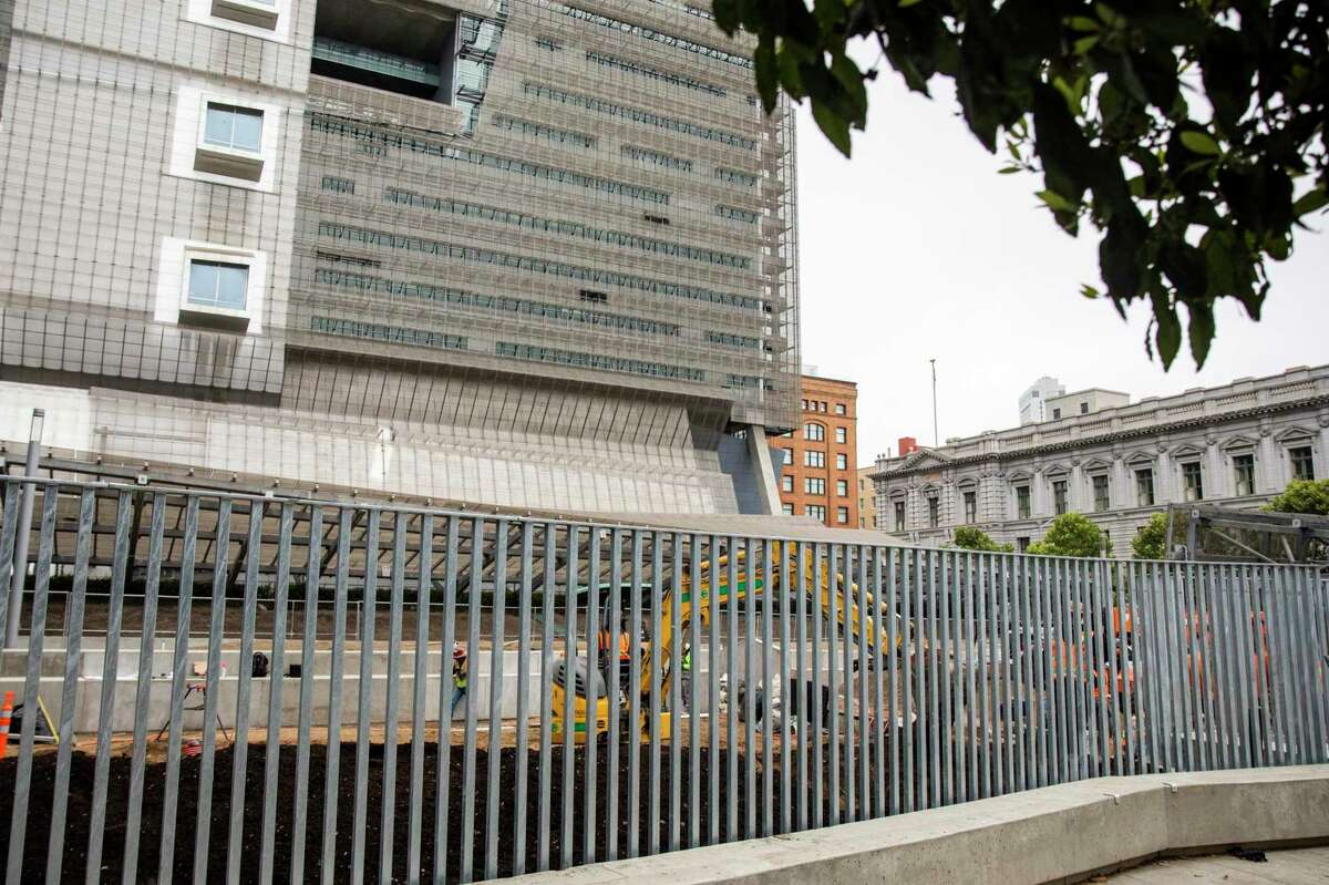 Construction crews work on a new plaza with a large metal fence near the Federal Building at Seventh and Mission streets in San Francisco. The stark unpleasant plaza has been torn out and is being replaced by a new design that includes a metal fence along Mission Street.