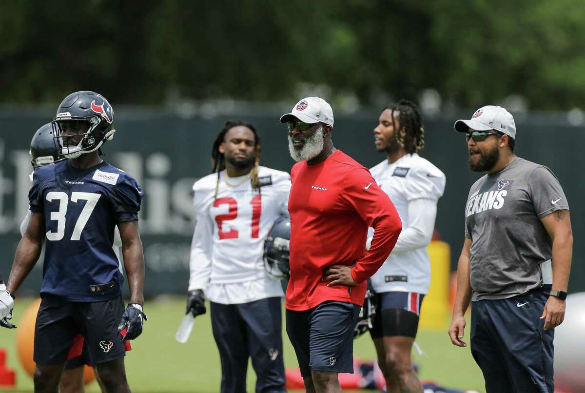 Texans linebackers coach Miles Smith, right, has followed his father Lovie, Houston's defensive coordinator, into the coaching profession.