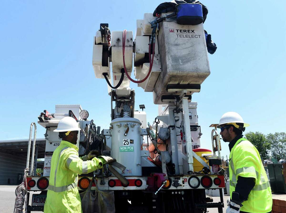 Linemen first class Brandon Sims, left, and Nelson Lopez demonstrate the securing of a transformer at the United Illuminating Operations Center in Orange on June 18, 2021.