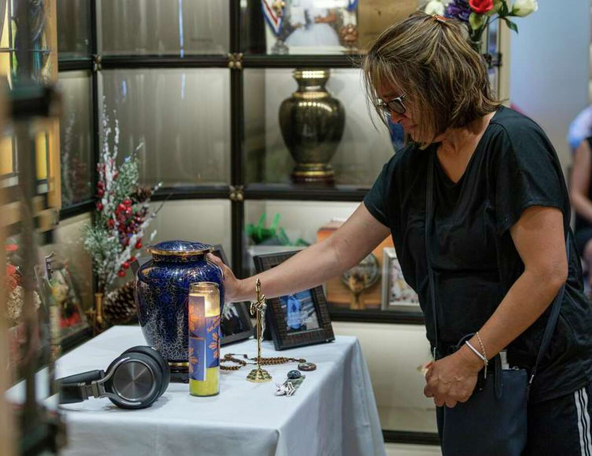 Cassandra Quinto-Collins touches the urn of her son Angelo Quinto at Antioch's Holy Cross Cemetery.