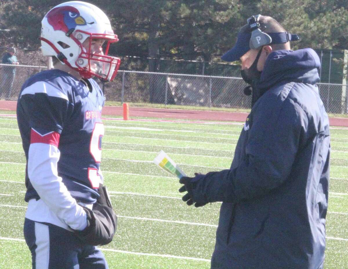 Wil Strickler (left) and Big Rapids football coach Mike Selzer go over plays during a 2020 game. (Pioneer file photo)
