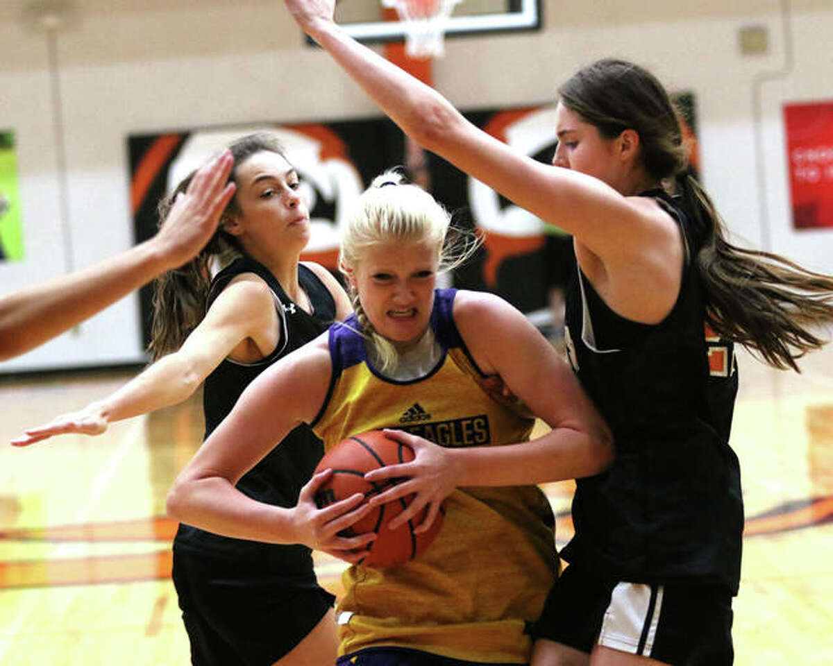 CM's Claire Christeson (middle) drives to the basket between Edwardsville's Elle Evans (right) and Kaitlyn Morningstar before falling to the court with a torn ACL in a summer shootout girls basketball game Tuesday at Lucco-Jackson Gym in Edwardsville.