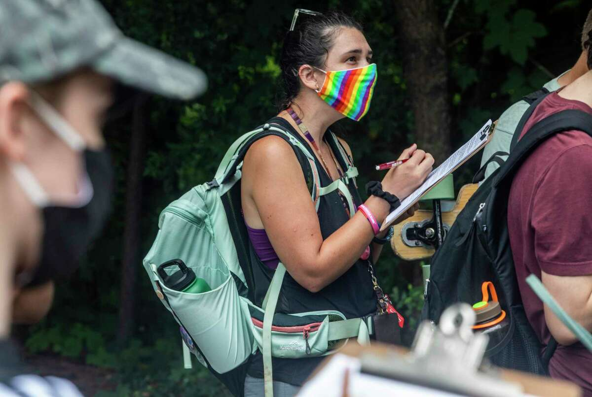 Sarah Puls, a natural resources major, center, takes notes during an outdoor class of about 20 masked students on the campus of North Carolina State University,