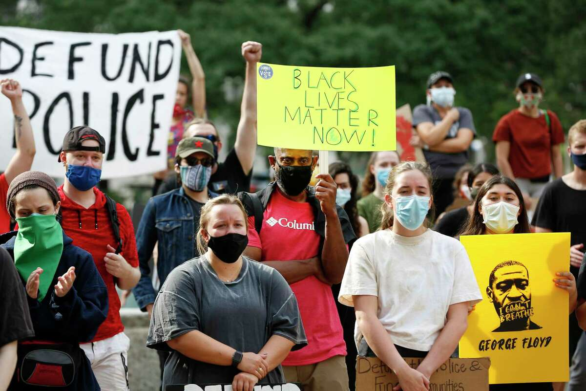 Protesters hold signs during a rally in support of amendments to eliminate police misconduct to the city budget Wednesday, June 10, 2020, in Houston.