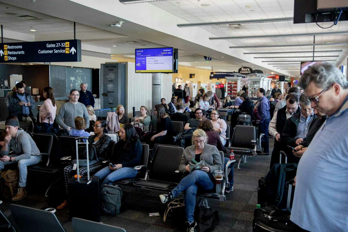 Travelers crowd into a gate while waiting to board their flight at Oakland International Airport in January.