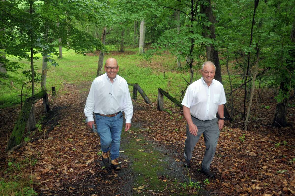 Aspetuck Land Trust President Bill Kraekel, left, and Easton First Selectman David Bindelglass take a tour of a property the land trust will receive following a recent grant, in Easton, Conn. July 1, 2021. The property will add to the land trust's Warner Angler Preserve along the Mill River.